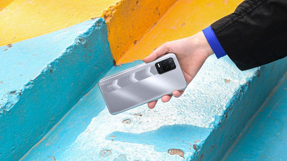 Na zdjęciu, trzymany w dłoni, smartfon realme narzo 30 5G
