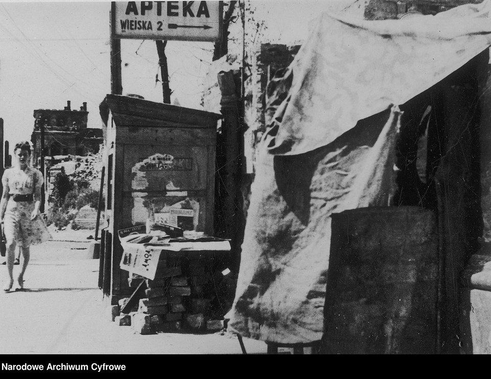 Życie codzienne na ulicach Warszawy. Ulica Piękna. Widoczny szyld apteki przy ul. Wiejskiej 2, 1947-48.