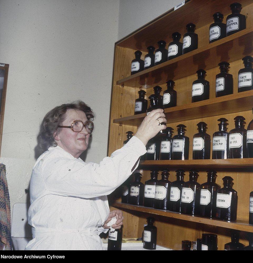 Krystyna Kordzik z Józefowa, farmaceutka pracująca w aptece w Międzylesiu, stoi przy regale z odczynnikami chemicznymi do sporządzania leków recepturowych, 1980 r.
