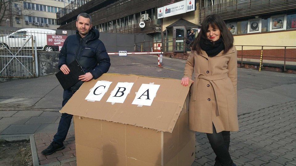 Maciej Konieczny i Dorota Olko z kartonowym CBA przed siedzibą PiS