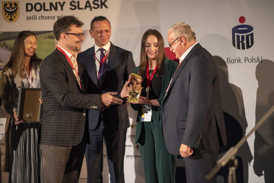Andrzej Łaniak i Elżbieta Łaniak, zwycięzcy konkursu Promotor Przedsiębiorczości Rodzinnej odbierają nagrodę z rąk Dariusza Szkaradka prezesa NFG, który wręcza ją w imieniu fundatora Martina Kaczmarskiego prezesa Kaczmarski Group.