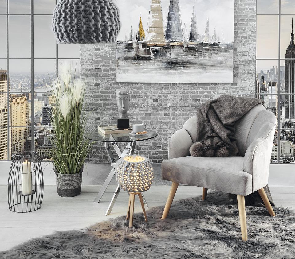 Minimalistyczną aranżację dopełniają dodatki o ciekawej fakturze – miękki dywan i pleciona lampa.