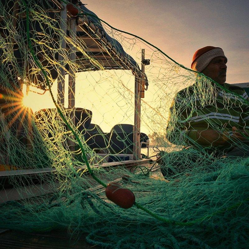 Mending fishing nets by Rolando Batacan (Qatar).jpg