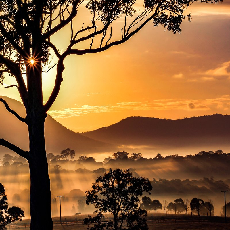 Sunrise over valley and mountains by Justin McKinney (Australia).jpg