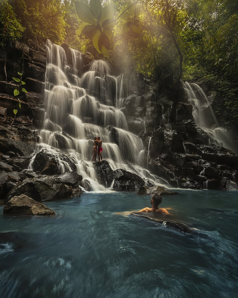 Young couple kissing under the Kanto Lampo waterfall, Indonesia (Nofianto/AGORA images)