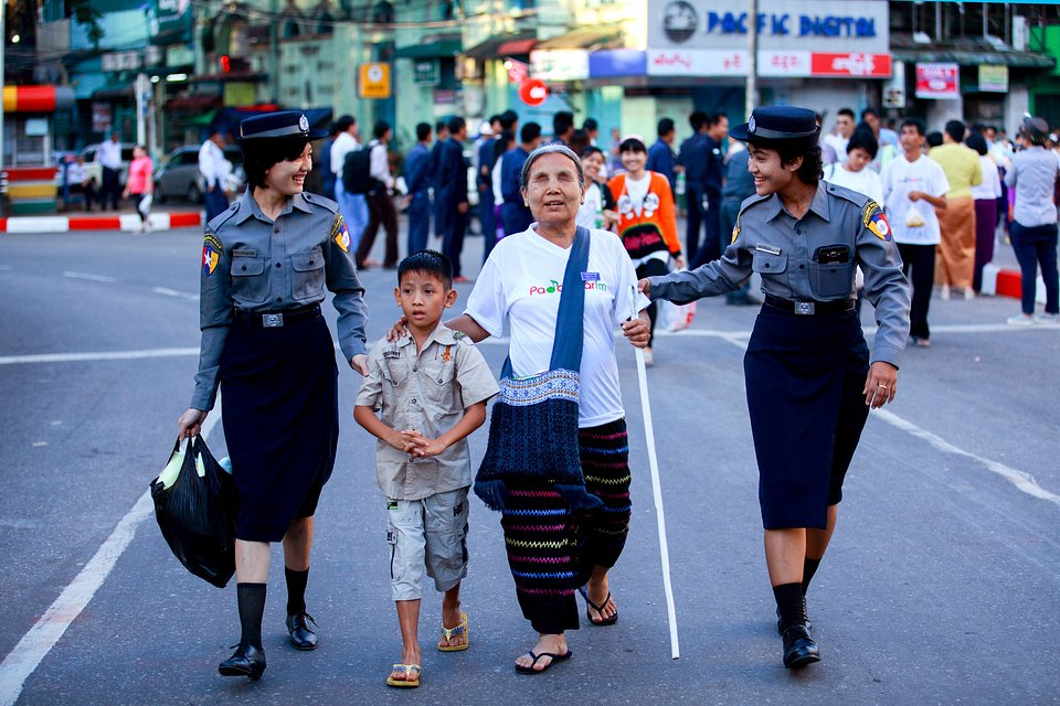 Two policewomen help a blind lady crossing the street in busy Yangon (Ye Kyaw Thu/AGORA images)