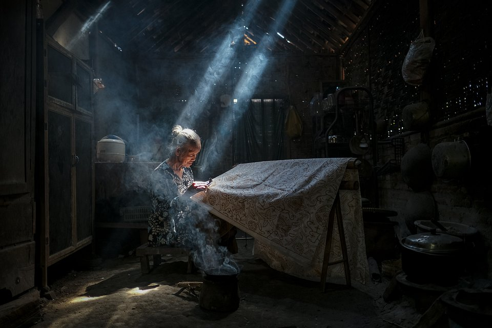 Batik making in Yogyakarta, Indonesia. Batik is technique of wax-resist dyeing applied to whole cloth. The lady pictured has been mastering this art for the past 35 years. With this picture the photographer hopes to keep this tradition alive. (Bimo Pradityo/Agora)