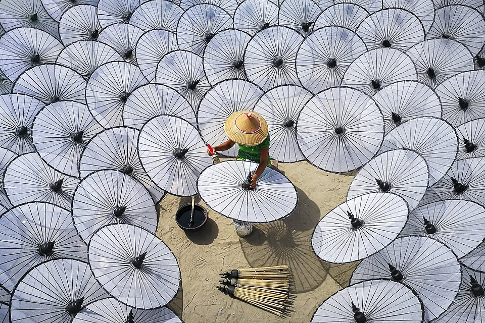A woman makes traditional umbrellas at a factory in Mandalay, Myanmar. The production of a traditional umbrella cannot be done by a single person or within a day: there is a division of labor in the making of a single umbrella. Each worker is responsible for different parts to finish one umbrella. (Aung ThuYa/Agora)