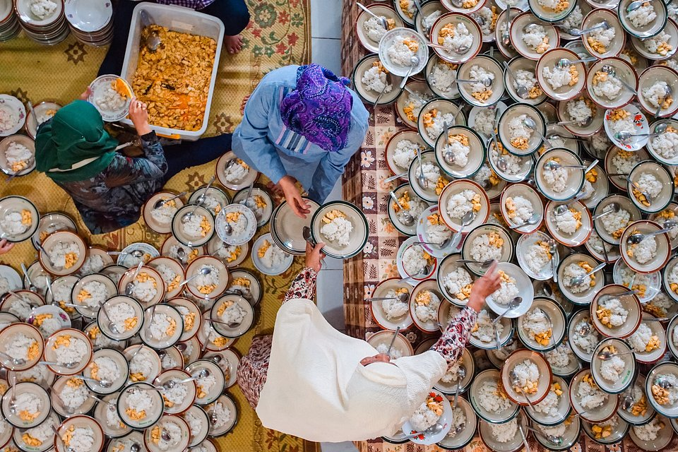Three volunteers serve 1000 plates of chicken and rice prepared for the Iftar, an evening meal in which Muslims end their daily Ramadan fast at sunset. (Dharma Kurniawan/Agora)