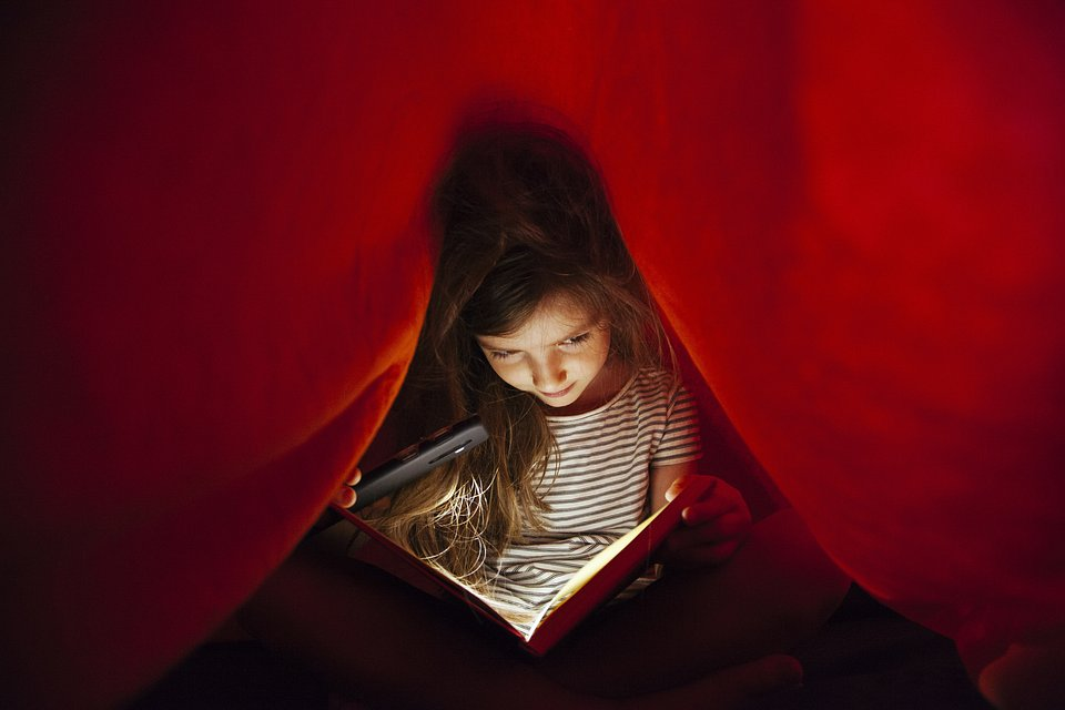 Bedtime stories under the red sheets for this little girl in Spain (Beatriz Vera/AGORA images)