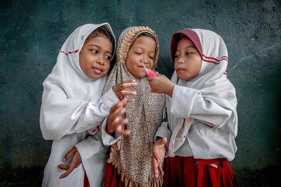Pupils sharing an ice lollipop during playtime break (Rustam Awat/AGORA images)