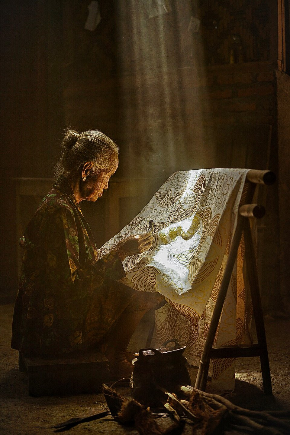 As the sunlight gets through the ceiling, this woman completes her Batik painting, one of Indonesia's most ancient craft (Lety Liza/AGORA images)