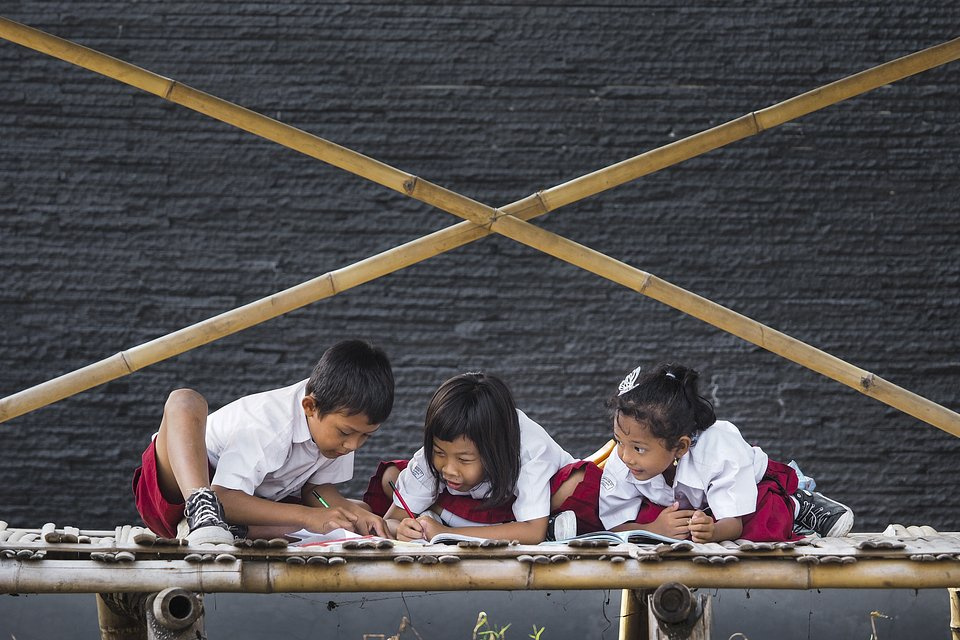 These children were photographed finishing their homework on the street, as it was due in the nick of time. (Asad Khalid Sungkar/Agora)
