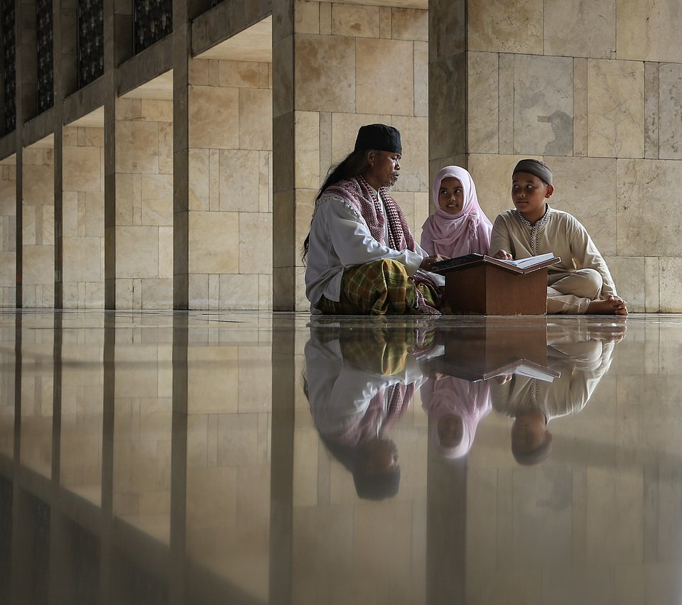 Two young children learning how to read the holy Qur'an and becoming more familiar with their religion. (Dandi Rahman/Agora)