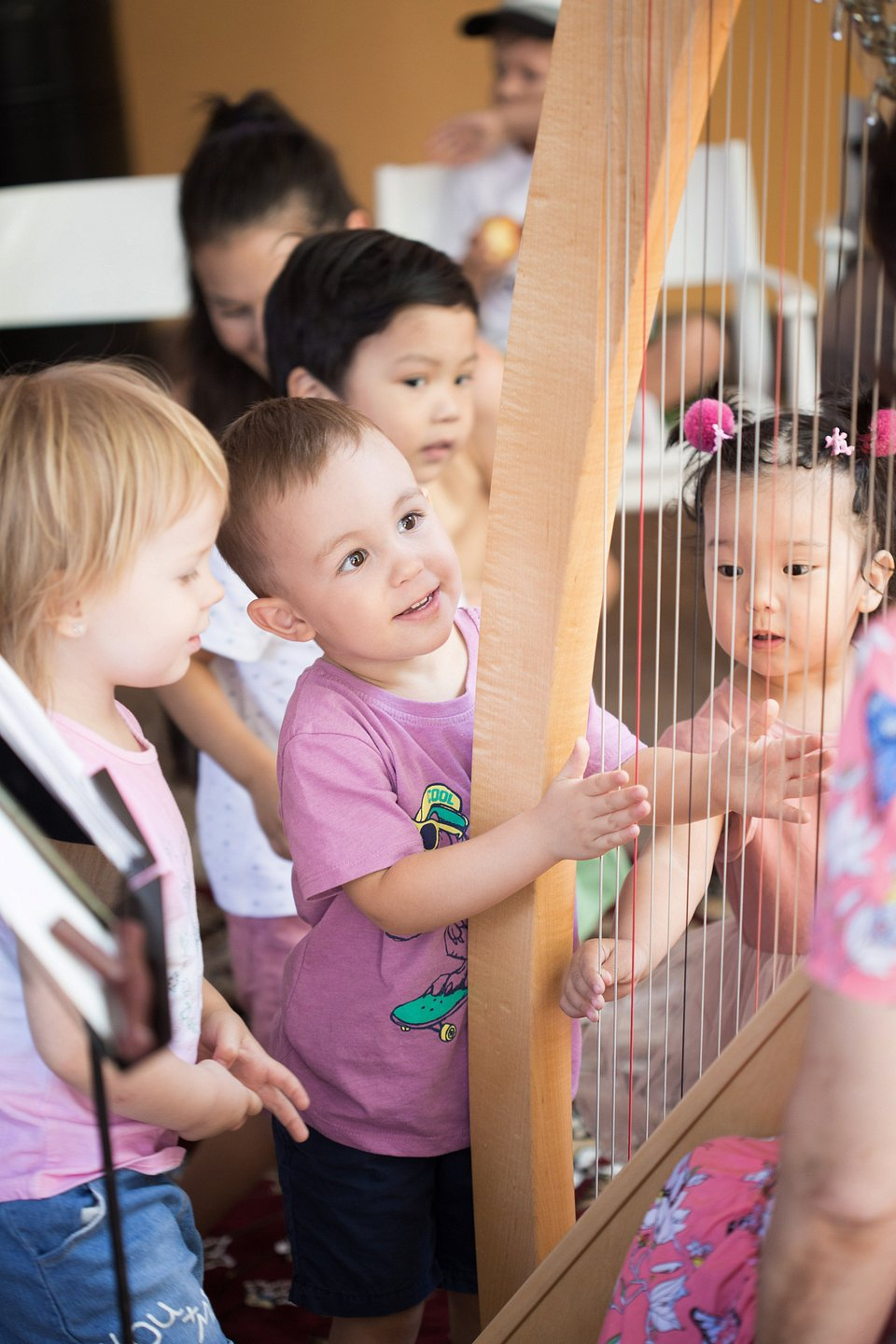 Children gathered around a harp, showing pure delight in the angelic instrument. (Gaukhar Yerkimbekova/Agora)