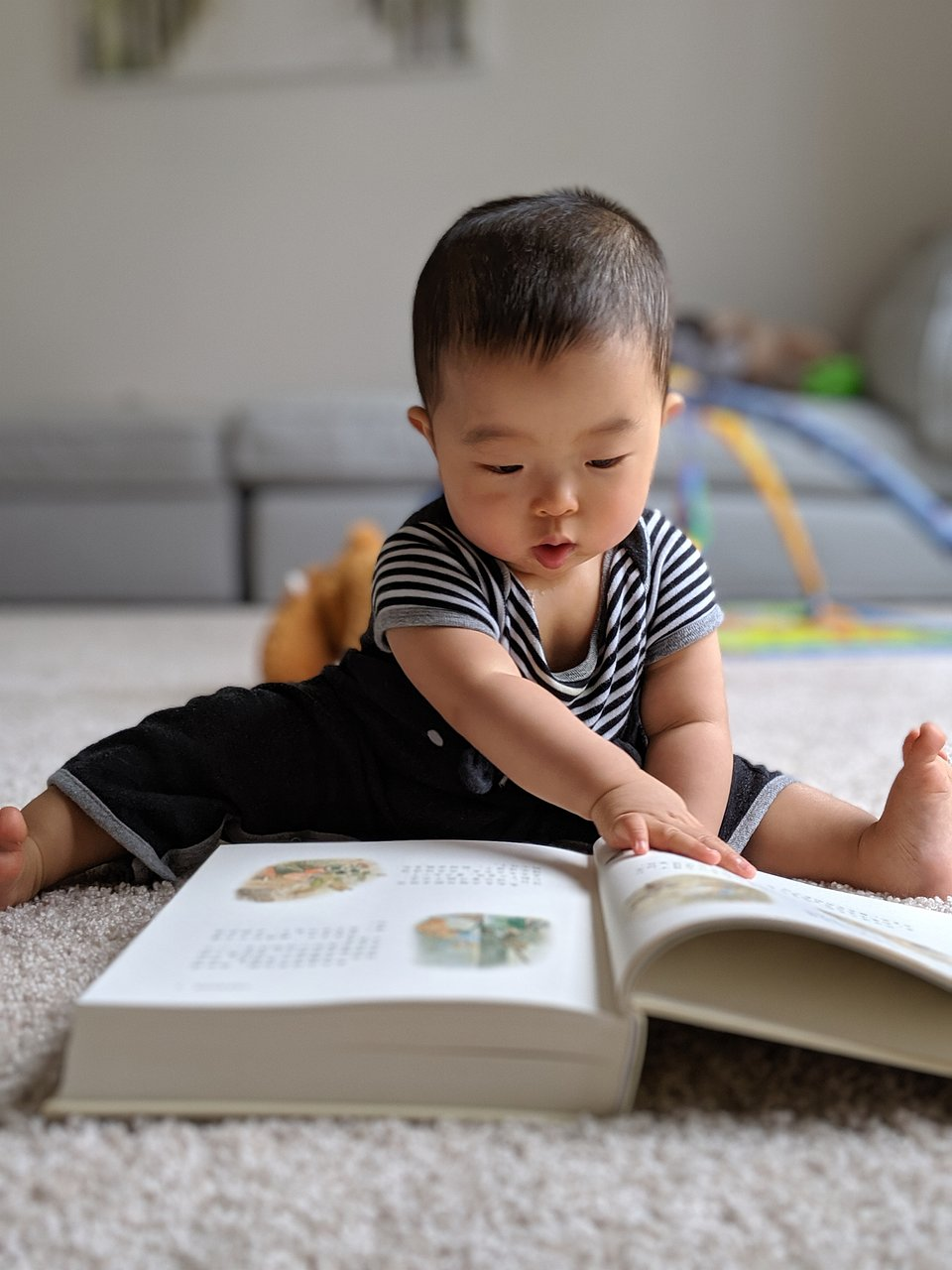A baby attempting to read quite a thick book. We wonder what he thinks about it. (Haimei Li/Agora)