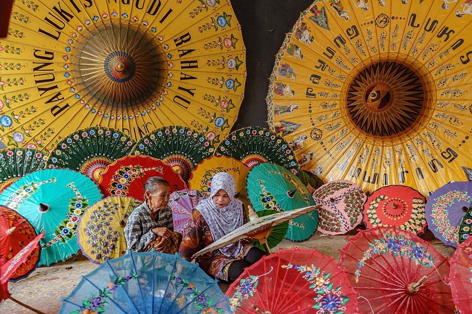 A senior painter is photographed here teaching a junior how to paint umbrellas. (John Harris Nadeak/Agora)