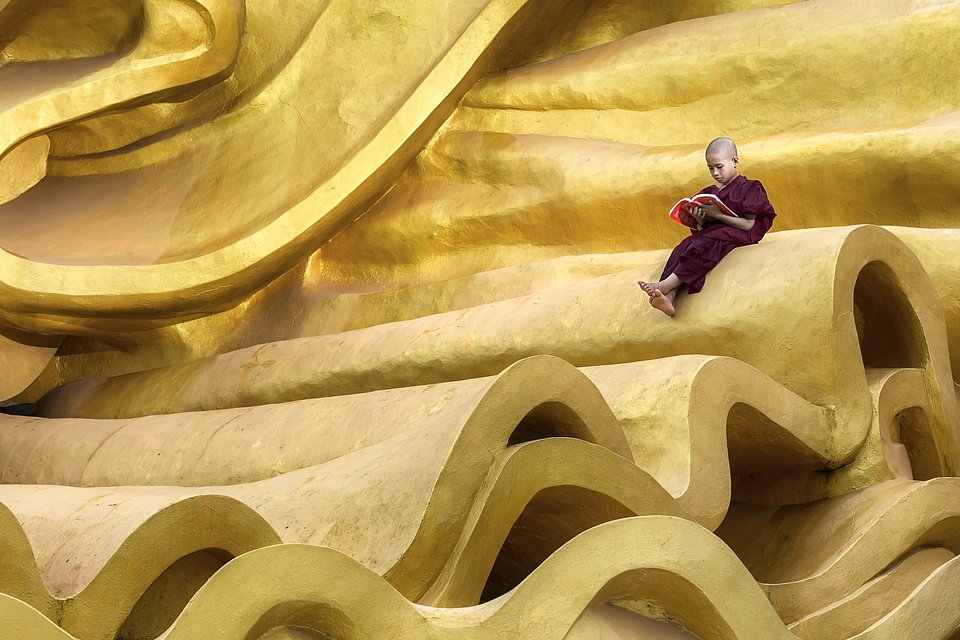 A young student comfortably sitting on a large golden structure, reading quietly. (Kyaw Myint Than/Agora)