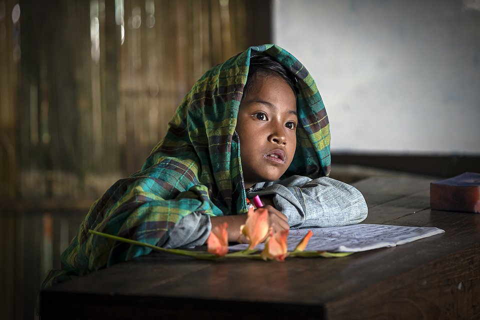 A child learning in her classroom, her face illuminated by natural gloomy light. (Naing Tun Win/Agora)