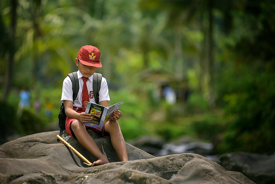 Each day, on his way home from school, the child in the photograph pauses on the rocks. He repeats the lessons he learns in school while enjoying nature. (Pepi Perdiansyah/Agora)