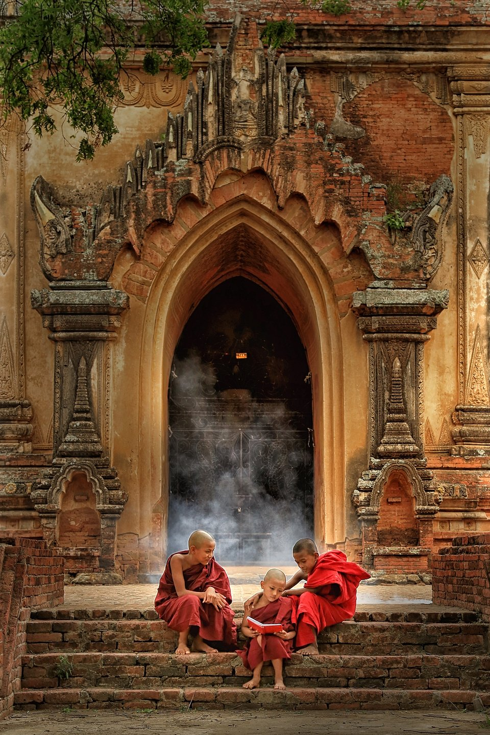 Young monks sitting on the steps of an ancient building, reading together. (Phyu Aye Pwint/Agora)
