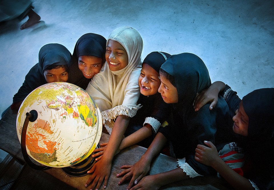 Children surrounding a luminous globe as it lights up their smiling faces. The globe evokes learning about the planet and the environment, and makes a subtle reference to global warming. (Pranab Basak/Agora)