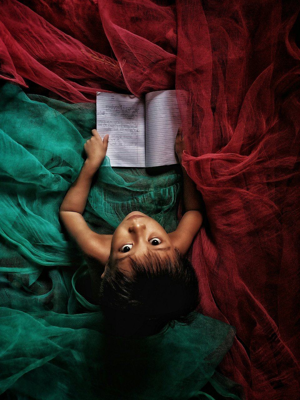 A little boy reading and writing in his journal, before he goes to sleep. (Robert Marrel Dela Vega/Agora)