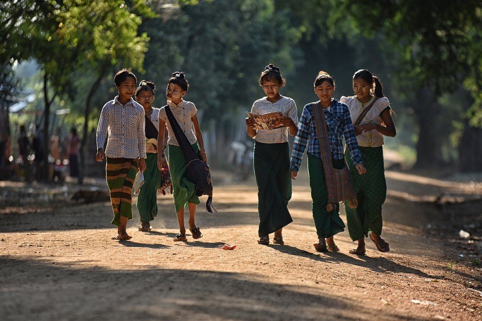 A group of students walking to class in the morning, illuminated by sunshine. (Thant Zin/Agora)