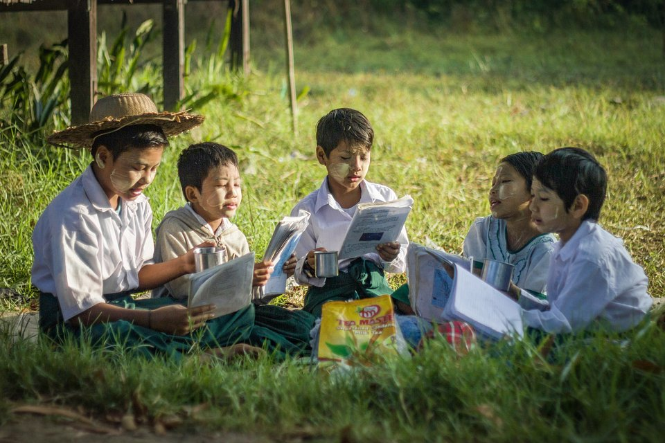 Five excited students, sitting in a field and reading together in Ayeyarwady, Myanmar. (Thet Nanda Aung/Agora)