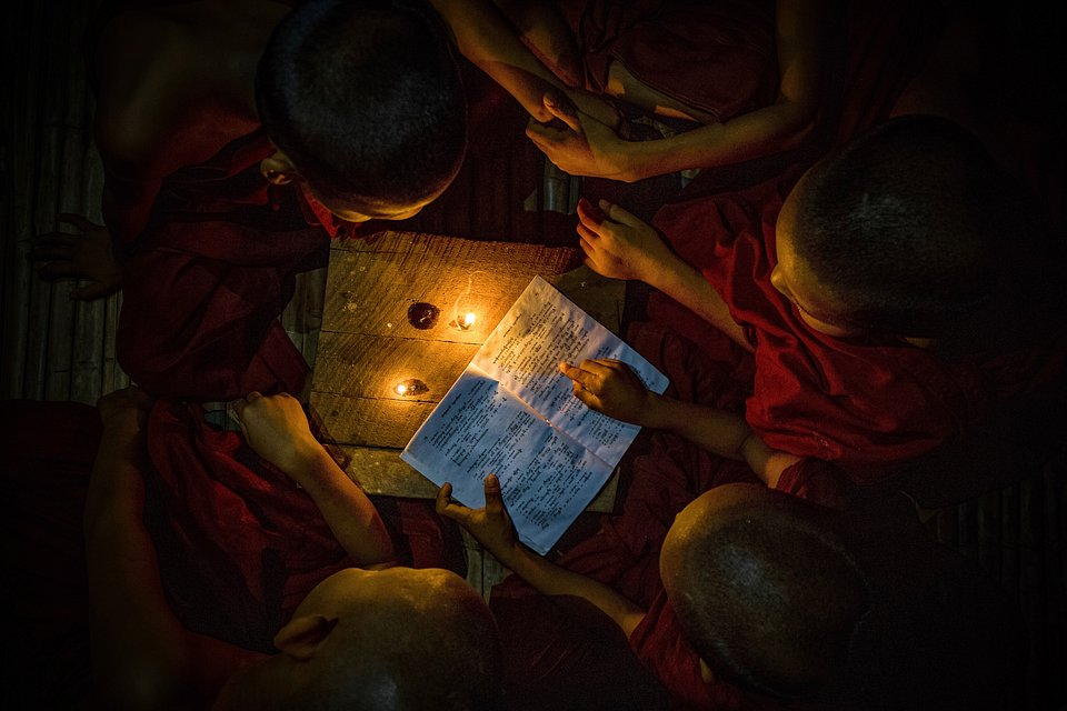 Children reading under candlelight, sharing their knowledge with one another. (Sithu Kyaw/Agora)
