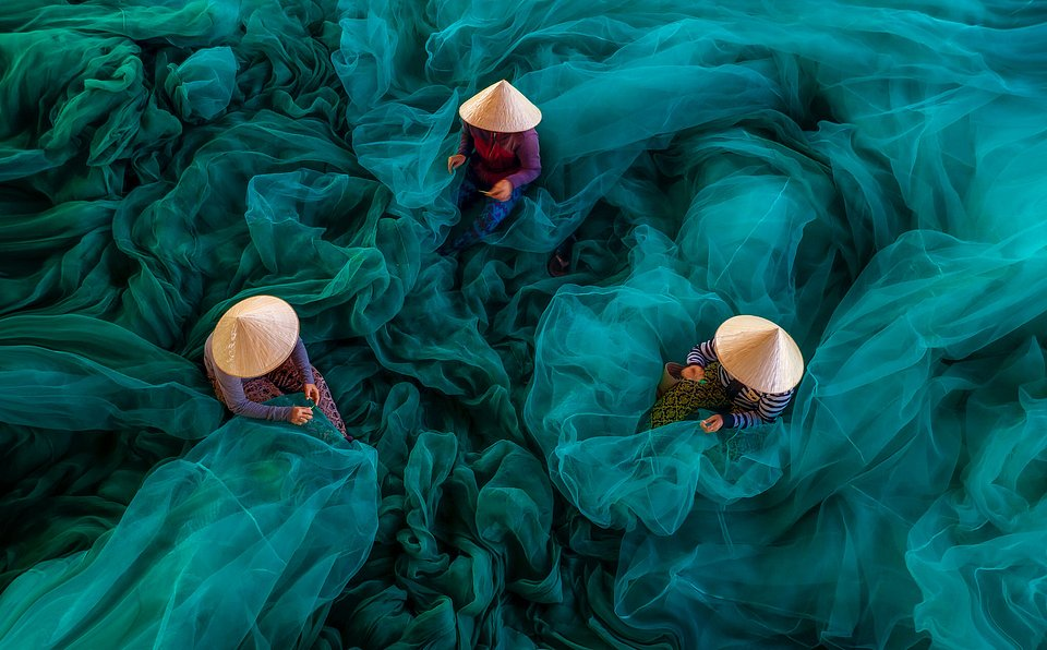 Women performing net mending work after the fishing boats return. They are extremely hardworking, proven by the constant movement between ports they must make to serve their work. (Khánh Phan/Agora)