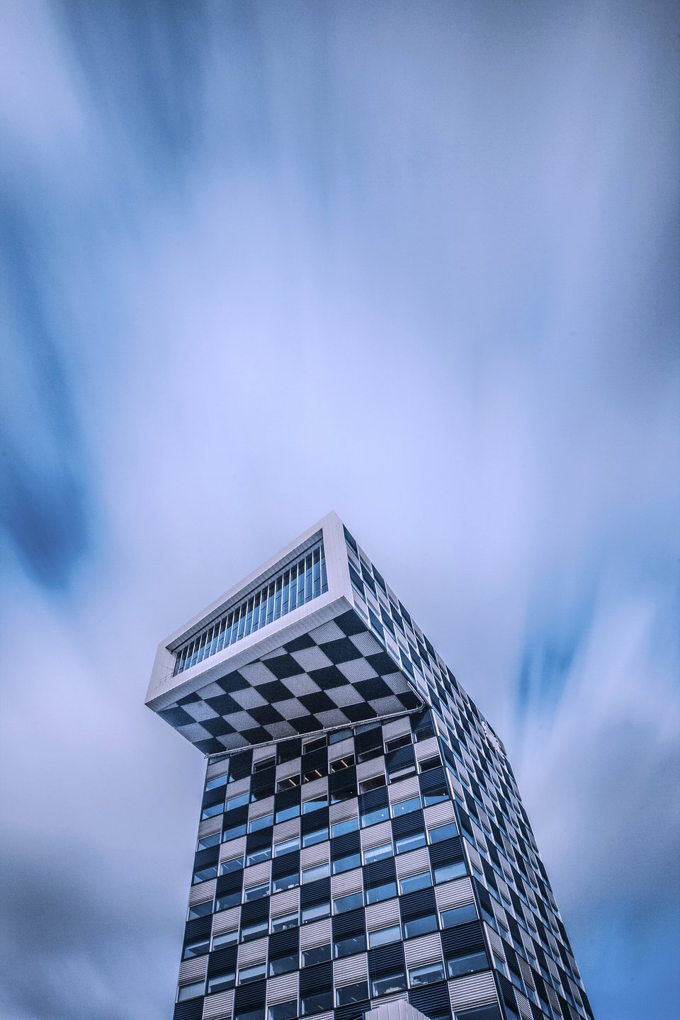 The unique architecture of this building in Milan, Italy stands out among the blue and the moving clouds of the sky behind it. (Rockson Armaah/Agora)
