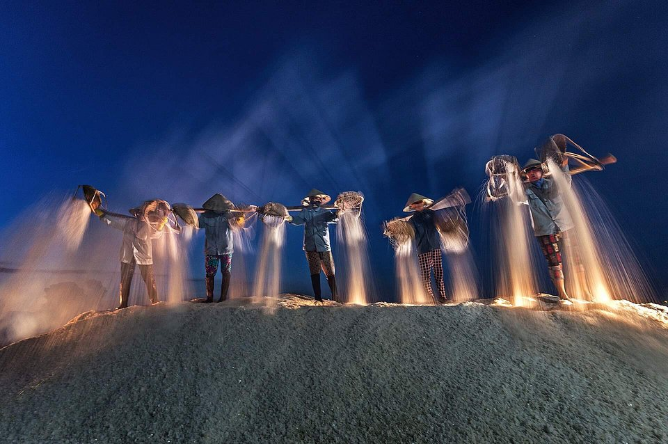Workers in Vietnam harvesting salt at night to avoid sun exposure. (Đỗ Tuấn Ngọc/Agora)
