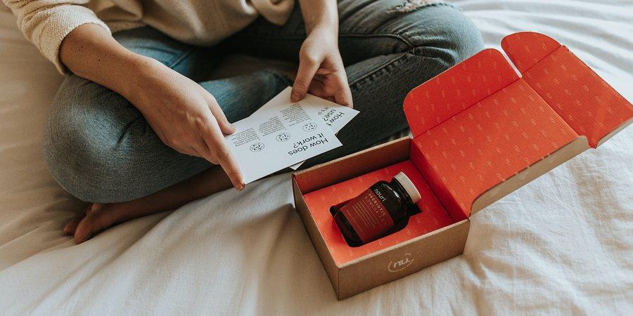 Customer Experience w e-commerce. W co powinny inwestować sklepy? - kobieta siedzi na łóżku przy otwartej paczce i czyta ulotki.